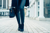 Details of women's clothing. Closeup of female legs in black pants and boots. Woman walking in the city, low-angle shooting, cold toning.