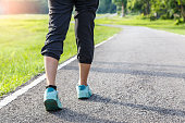 Closeup of female shoe runner feet running on road with nature background, fitness woman