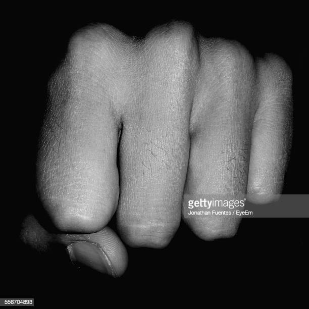 Close-Up Of Fist Over Black Background