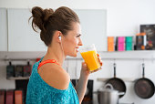 In her modern kitchen, a woman in profile is about to drink her freshly-made smoothie, which is packed with vitamins. A healthy lifestyle is so much fun.