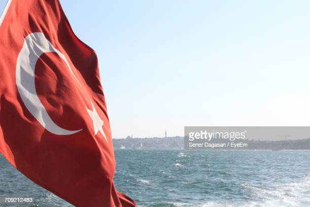 Close-Up Of Flag Of Turkey Waving Over Sea Against Clear Sky