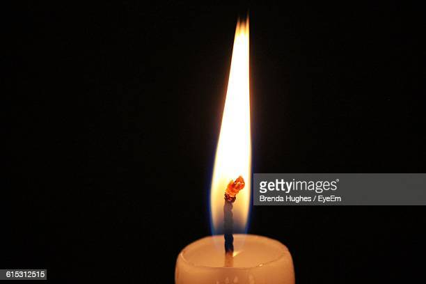 Close-Up Of Flame On Candle Against Black Background