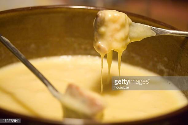 Close-up of forks dipping into a fondue pot