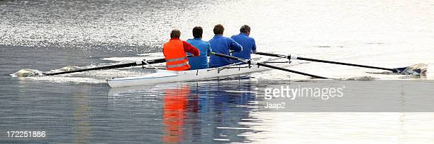 Close-up of four men rowing in a canal