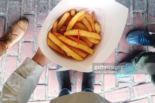 Close-Up Of French Fries In Paper Cone And Low Section Of Men On Background