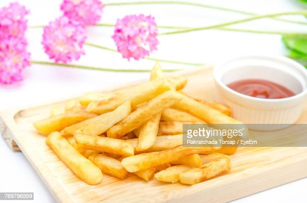Close-Up Of French Fries With Sauce On Cutting Board