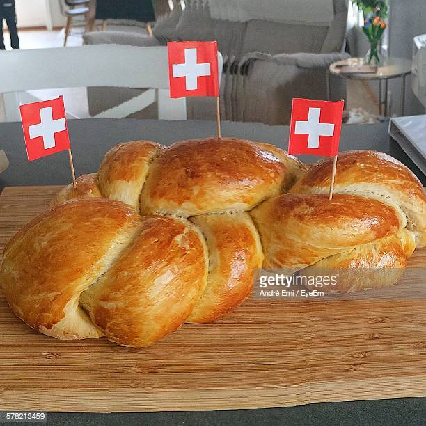 Close-Up Of Fresh Breads With Swiss Flags On Wooden Table