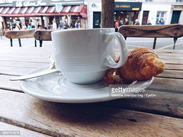 Close-Up Of Fresh Coffee And Croissant Served On Table At Sidewalk Cafe