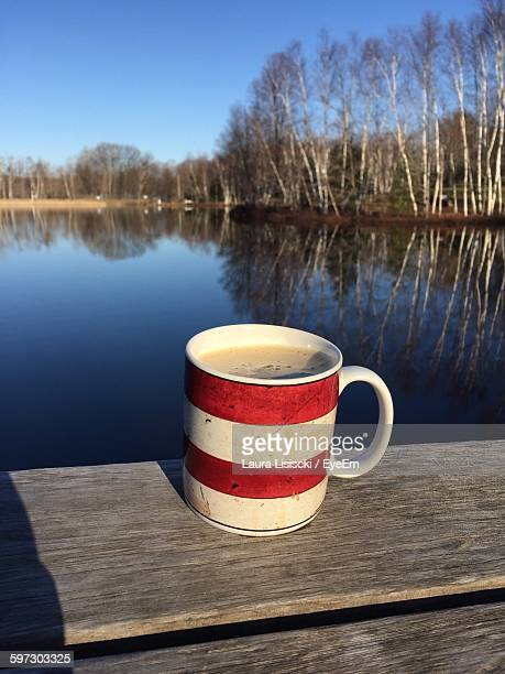 Close-Up Of Fresh Coffee In Cup On Pier By Lake