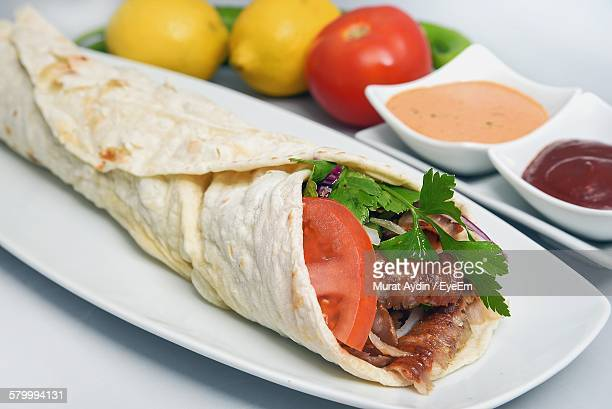 Close-Up Of Fresh Kebab Shawarma Served In Plate With Savory Sauces