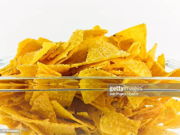 Close-Up Of Fresh Nacho Chips In Glass Bowl Against White Background