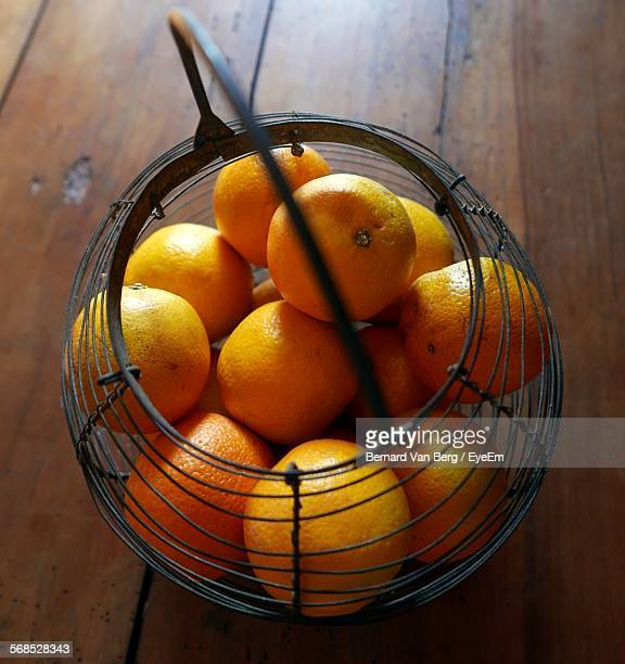 Close-Up Of Fresh Oranges In Metal Basket On Hardwood Floor