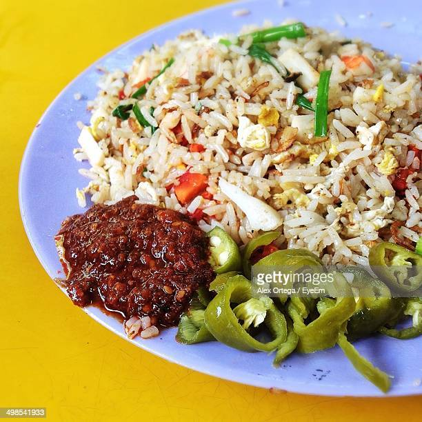 Close-up of fried rice with schezwan sauce and capsicum in plate