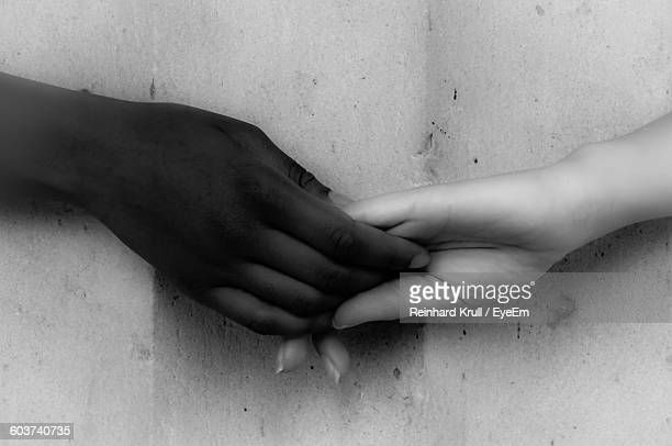 Close-Up Of Friends Holding Hands Against Wall