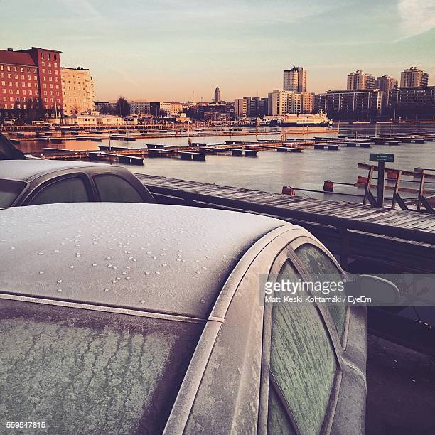 Close-Up Of Frozen Car Roof By Harbor Against City During Sunset