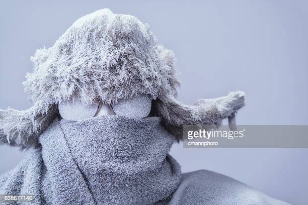 Close-up of frozen man in parka, hat and scarf