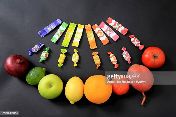 Close-Up Of Fruits And Candy Wrappers On Black Background