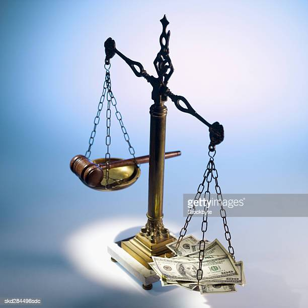 Close-up of gavel and American dollar notes balancing scales of justice