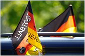 Close-up of German World Cup flags hanging on car against blurred background