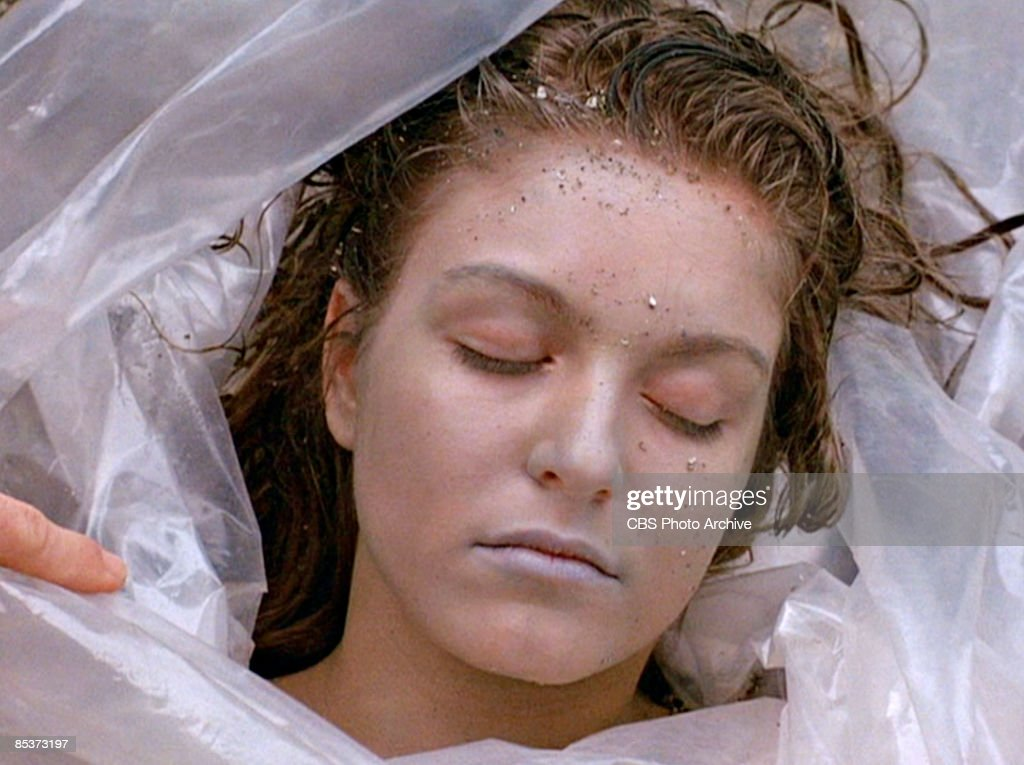 Close-up of German-born American actress Sheryl Lee (as the deceased Laura Palmer) lies, wrapped in a plastic sheet, on a rocky beach in a scene from the pilot episode of the television series 'Twin Peaks,' originally broadcast on April 8, 1990.