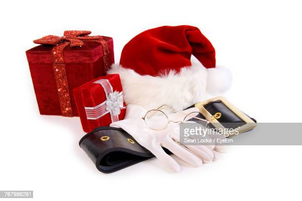 Close-Up Of Gifts By Hat Over White Background