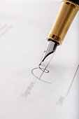 Close-up of gilded fountain pen signing contract, document on white background. Vertical image.