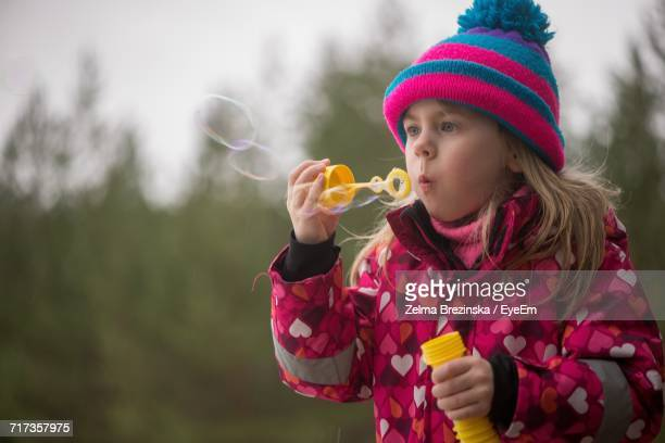 Close-Up Of Girl Blowing Bubbles