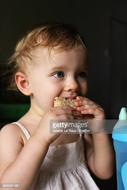 Close-Up Of Girl Eating Sandwich At Home