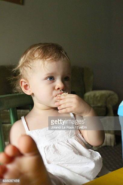 Close-Up Of Girl Eating Sandwich While Sitting On Chair At Home