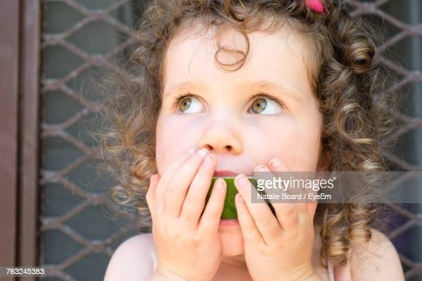 Close-Up Of Girl Eating Watermelon Against Window Outdoors