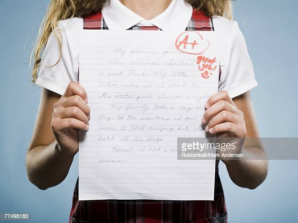 Closeup of girl holding A plus paper