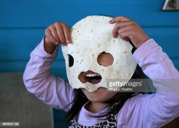 Close-Up Of Girl Holding Flat Bread With Holes Over Face