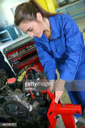 Closeup of girl in blue dungarees working at garage : Stock Photo