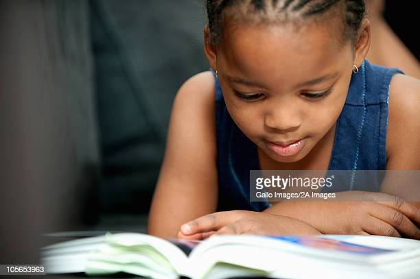 Close-up of girl (4-5) lying on front, reading book