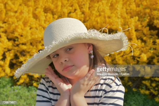 Close-Up Of Girl Posing While Wearing Sun Hat