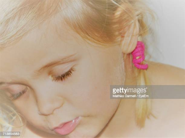 Close-Up Of Girl With Eyes Closed Against White Background