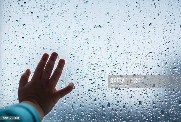 Close-up of girls hand on wet window