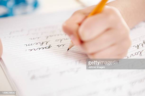 Close-up of girls hand writing on notebook