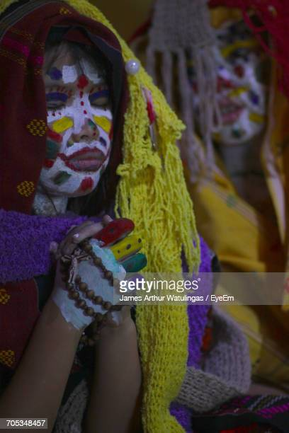 Close-Up Of Girls With Face Paint And Traditional Clothing Praying At Home