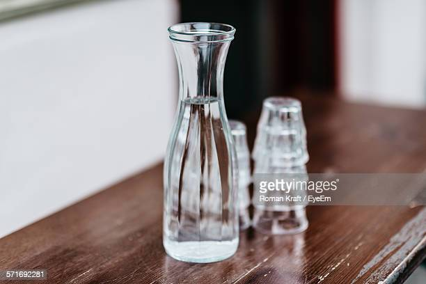 Close-Up Of Glass Bottle And Shot Glasses On Table