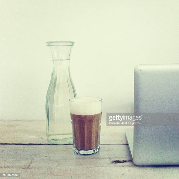 Close-up of glass jar with coffee and laptop