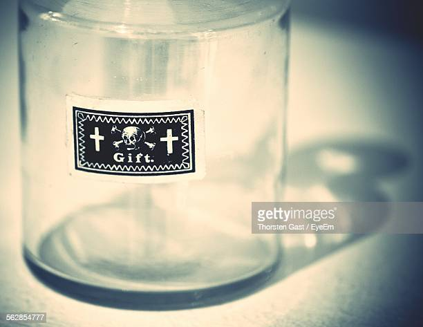 Close-Up Of Glass Jar With Label Of Skull And Cross Symbol