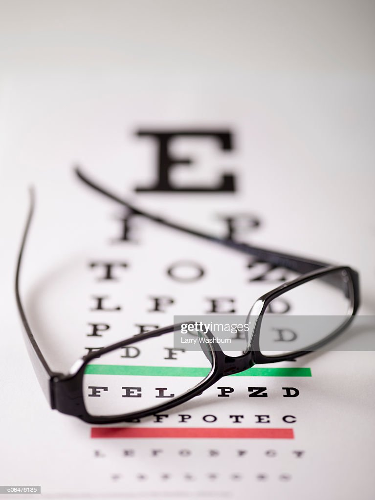 Close-up of glasses on eye exam chart