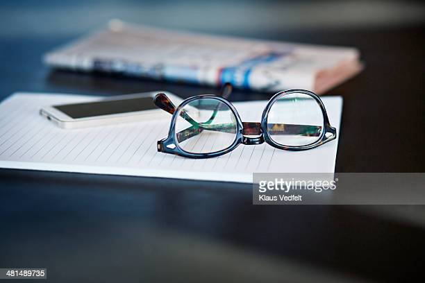 Close-up of glasses, phone and paper in back