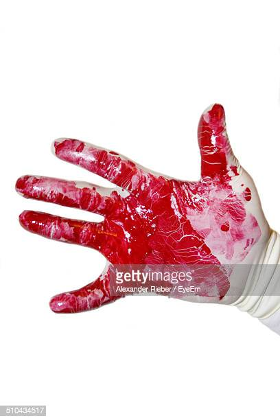 Close-up of gloved hand with blood over white background