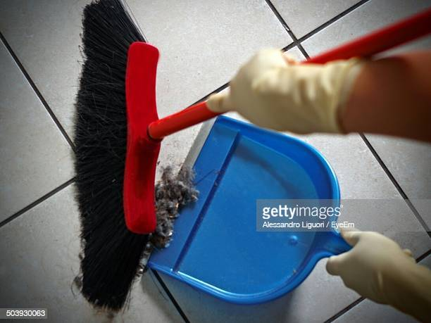 Close-up of gloved hands sweeping dust into dustpan tiled floor