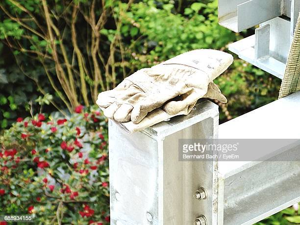 Close-Up Of Gloves On Metal By Plants