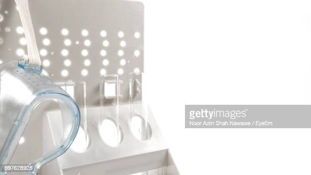 Close-Up Of Goggle And Test Tubes In White Rack Over White Background