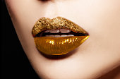 Closeup of gold artistic lips. Glitter upper lip and shiny lower lip. Makeup cosmetic image.