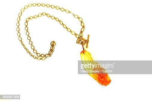 Close-Up Of Gold Chain And Pendant Over White Background